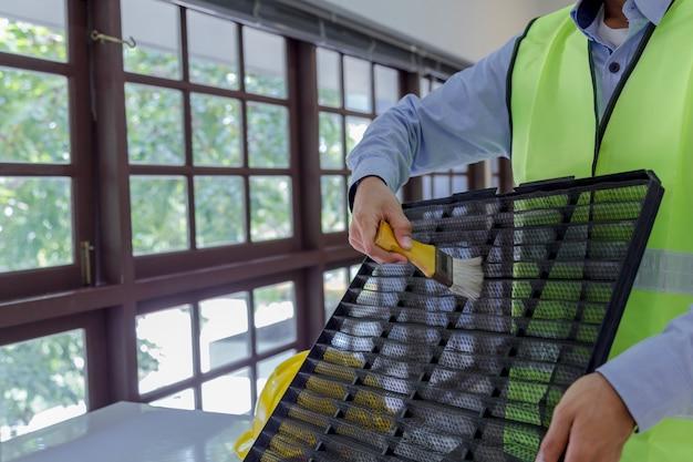 Technicien nettoie et répare le climatiseur mural Photo Premium