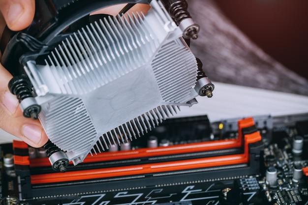 Technicien remet en place un ventilateur de refroidissement du processeur sur une carte mère d'ordinateur Photo Premium