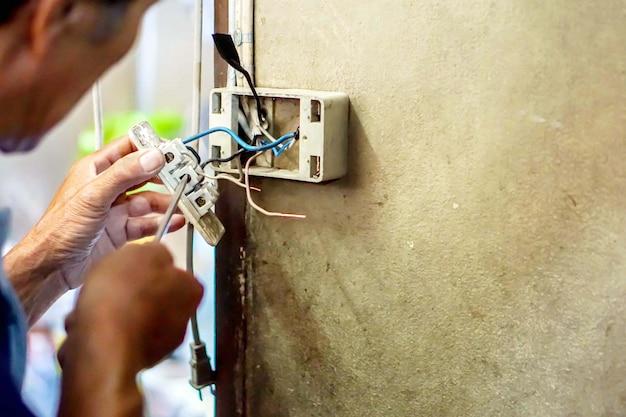 Technicien de réparation électrique agrandi tenant tournevis et fixant la prise électrique sur le vieux mur de bâtiment. Photo Premium