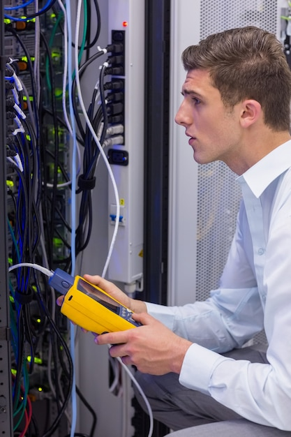 Technicien sérieux utilisant un analyseur de câble numérique sur serveur Photo Premium