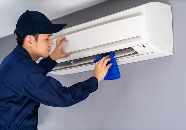 Technicien service nettoyage climatiseur avec chiffon Photo Premium
