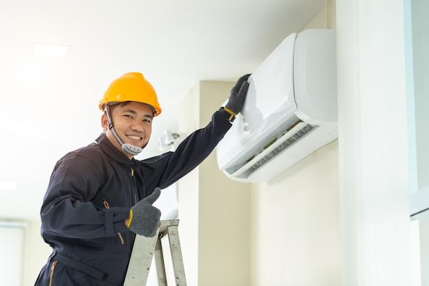 Technicien de sexe masculin réparant l'uniforme de sécurité du climatiseur à l'intérieur. Photo Premium