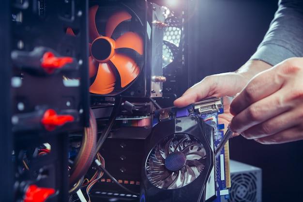 Technicien en train de réparer un ordinateur, processus de remplacement de composants sur la carte mère. Photo Premium