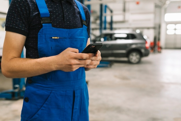 Technicien utilisant un téléphone dans un atelier de voiture Photo gratuit