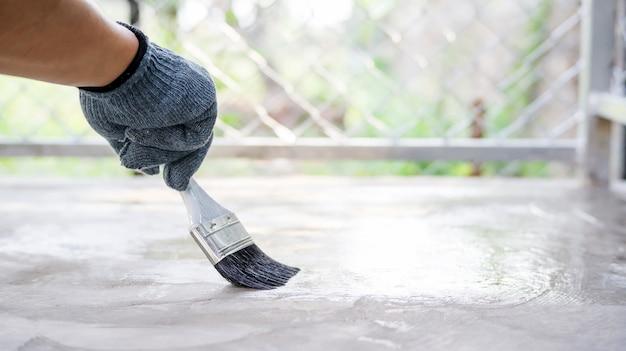 Technicien utilisant un vernis avec un sol en ciment. Photo Premium