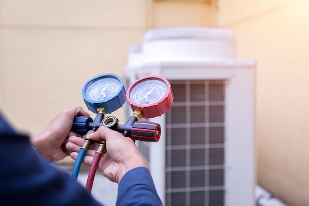 Un technicien vérifie le climatiseur et mesure le remplissage des climatiseurs. Photo Premium