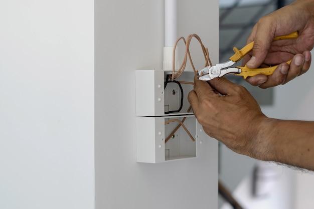 Les techniciens utilisent des pinces pour couper les fils afin d'installer des fiches et des interrupteurs sur la porte d'entrée. Photo Premium