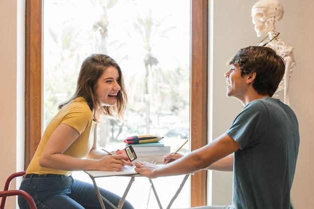 Teen couple rire et faire ses devoirs Photo gratuit