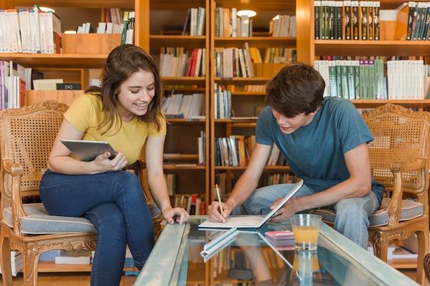 Teen couple avec tablette étudie dans la bibliothèque Photo gratuit