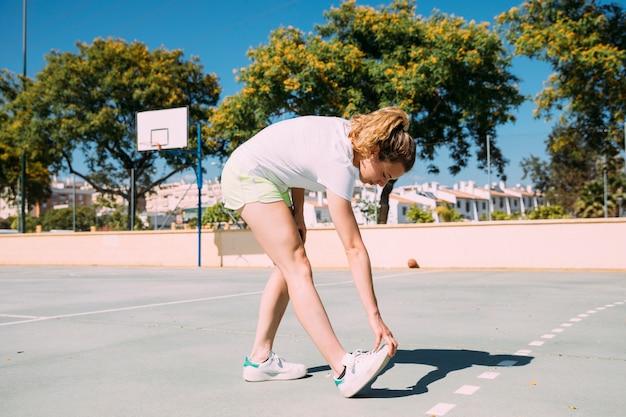 Teen écolière étirer les jambes au terrain de sport Photo gratuit