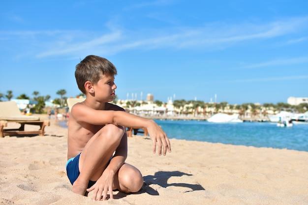 Teen est assis sur la plage et regarde la mer Photo Premium
