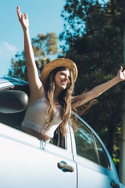 Teen fille agitant joyeusement à travers la voiture. Photo Premium