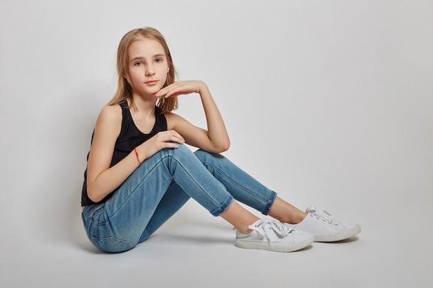 Teen fille assise sur le sol et rêvant Photo Premium