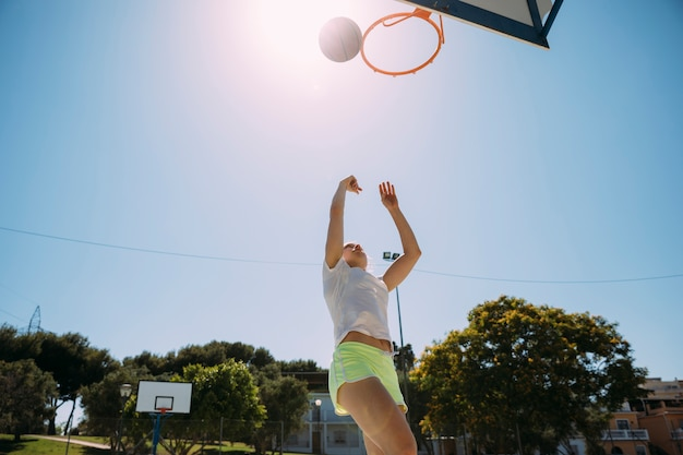 Teen Fille étudiante Jouant Au Basketball Au Terrain De Sport Photo gratuit