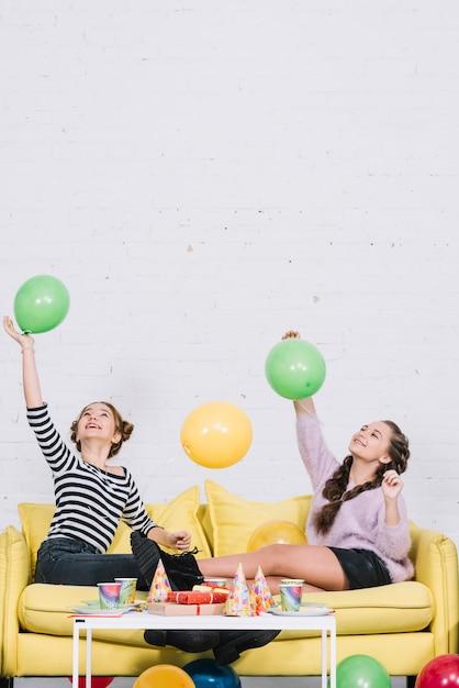 Teenage amies assis sur le canapé en jouant avec des ballons à la fête d'anniversaire Photo gratuit