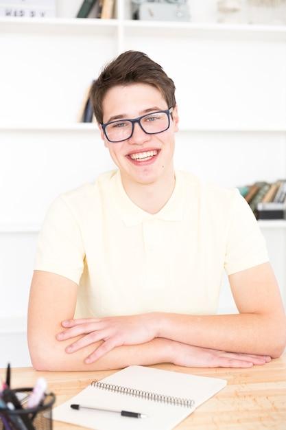 Teenage étudiant assis au bureau dans la salle de classe Photo gratuit