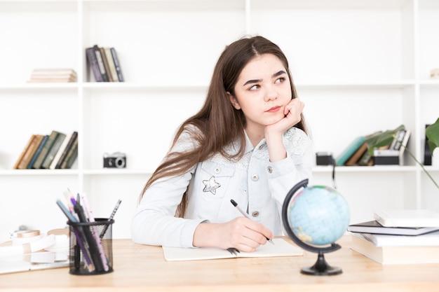 Teenage étudiant assis à table et écrit pensivement Photo gratuit