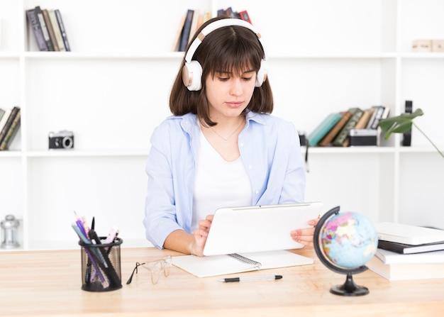 Teenage étudiant dans les écouteurs assis à table avec tablette en mains Photo gratuit