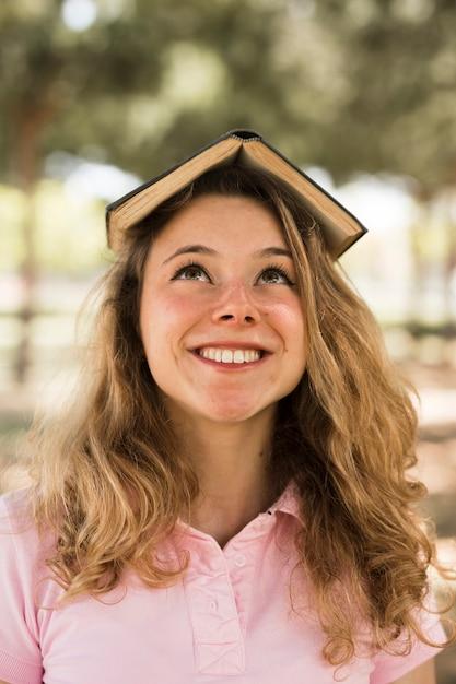 Teenage étudiant souriant avec livre sur la tête Photo gratuit