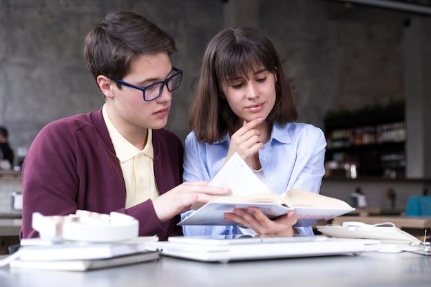 Teenage étudiants étudient avec un livre ouvert à table Photo gratuit