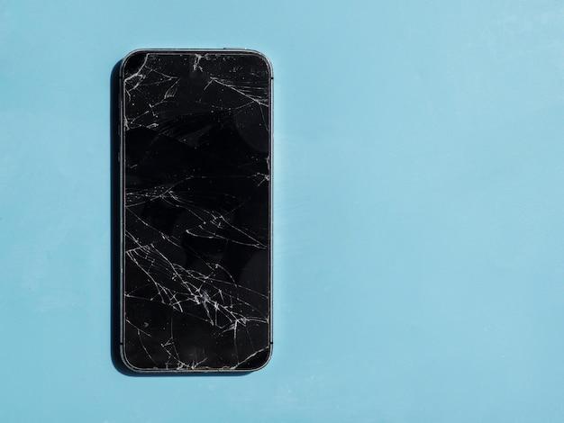 Téléphone avec écran cassé sur fond bleu Photo gratuit