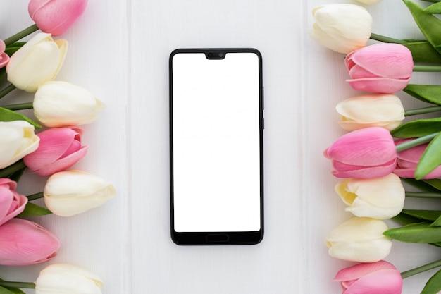 Un téléphone à écran prêt à être maquillé avec des fleurs de tulipes Photo gratuit