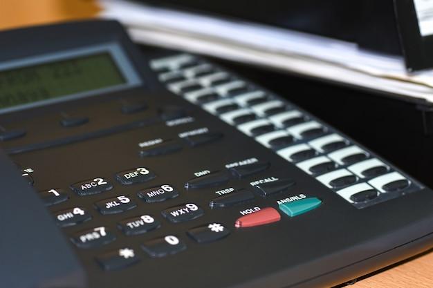 Téléphone fil noir avec touches et affichage sur le bureau du bureau Photo Premium