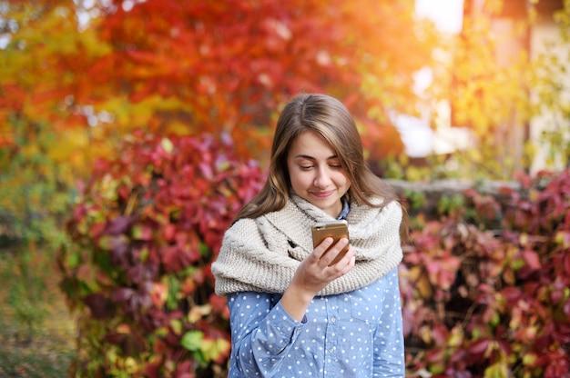 Téléphone intelligent femme automne écrivant sms sur téléphone mobile en automne Photo Premium