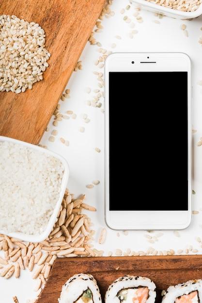 Téléphone intelligent avec sushi; riz cru et feuilleté Photo gratuit