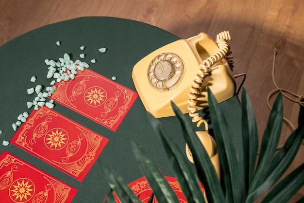Téléphone jaune latéral à côté des cartes de tarot rouge Photo gratuit
