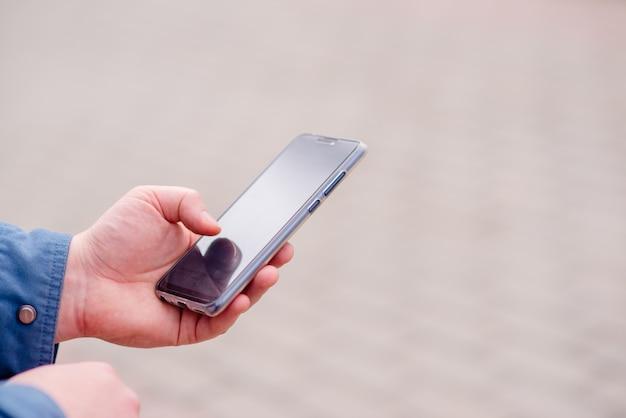 Téléphone mains homme jeune pour la recherche d'éduquer sur internet. banque en ligne, vue horizontale de la sécurité internet Photo Premium