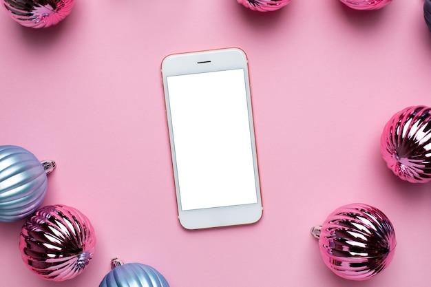 Téléphone Mobile Et Boules Bleues Et Roses De Noël Brillant Pour La Décoration Sur La Vue De Dessus De Fond Rose Photo Premium