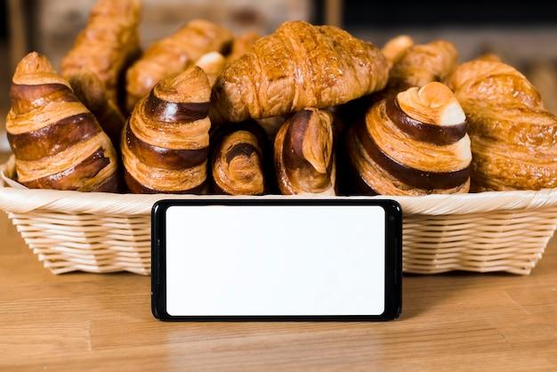 Téléphone mobile à écran blanc près du panier rempli de croissant cuit au four sur une table en bois Photo gratuit