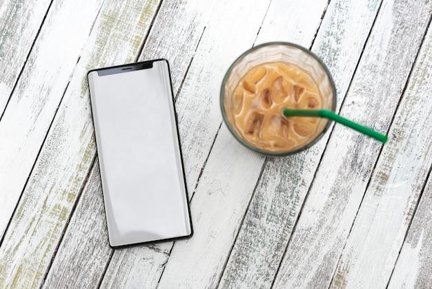 Téléphone mobile avec écran blanc et tasse à café sur une table en bois au café. Photo Premium