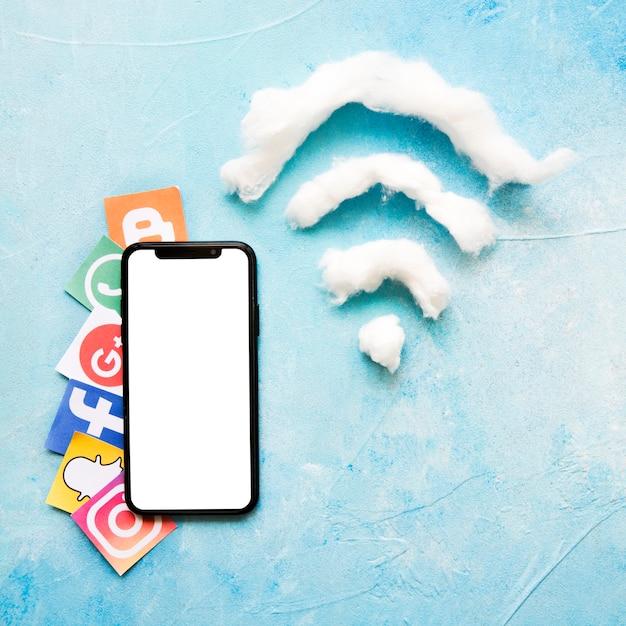Téléphone mobile et icône de médias sociaux vives à côté de symbole wi-fi en coton Photo gratuit