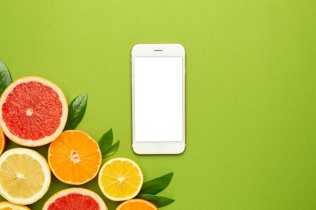 Téléphone Portable Et Agrumes, Technologie Et Plat De Fruits, Composition Minimale D'été Avec Pamplemousse, Citron, Mandarine Et Orange Photo Premium