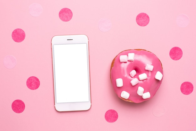Téléphone portable et beignet rose avec des guimauves sur un fond rose plat poser Photo Premium