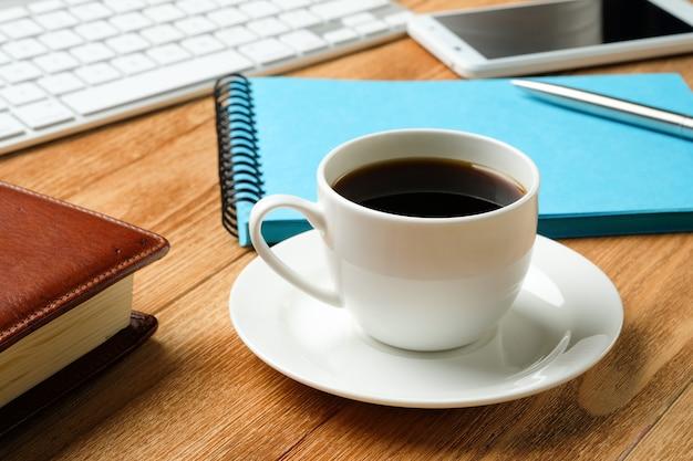 Téléphone Portable, Clavier D'ordinateur, Stylo Et Bloc-notes Pour Les Notes, Tasse à Café Sur Une Table En Bois. Photo Premium