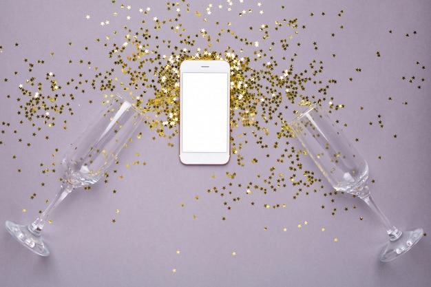 Téléphone portable avec confettis étoiles dorées sur violet Photo Premium