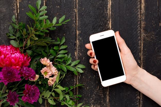 Téléphone portable dans une main féminine et un bouquet de fleurs sur un bois noir Photo Premium