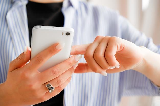 Téléphone portable dans les mains d'un pigiste de mode élégante. une jeune femme vêtue d'un t-shirt noir et d'une chemise à rayures, avec une belle manucure tenant le téléphone. Photo Premium