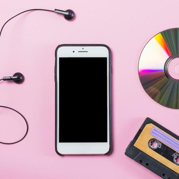 Téléphone portable avec écouteur; disque et cassette sur fond rose Photo gratuit