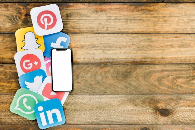 Téléphone portable avec écran blanc placé sur les icônes de réseaux sociaux sur la table en bois Photo gratuit