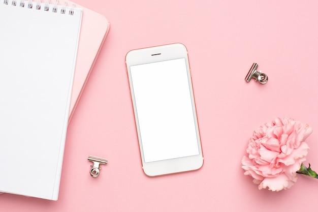 Téléphone portable avec fleur oeillet rose et cahier sur fond de marbre Photo Premium