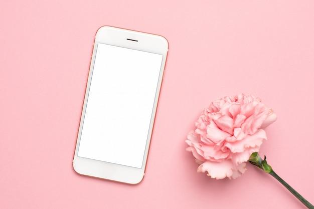 Téléphone portable avec fleur oeillet rose sur fond de marbre Photo Premium