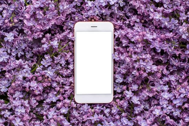 Téléphone portable et fleurs lilas. couleur de l'été et concept de vacances. Photo Premium