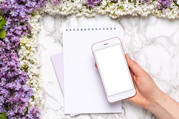 Téléphone portable à la main, cahier et cadre de fleurs blanches et lilas sur une table en marbre dans un style plat. Photo Premium
