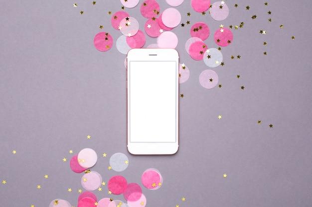 Téléphone portable, maquette, et, confetti rose, à, etoiles or, sur, gris Photo Premium