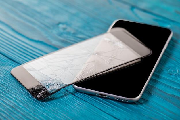 Un téléphone portable noir est un écran cassé sur fond de bois. Photo Premium