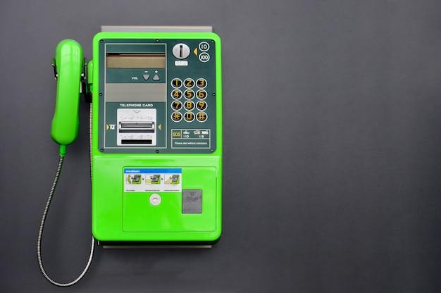 Téléphone public vert sur fond de couleur noire Photo Premium